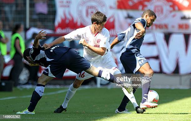 Dennis Mast of Halle challenges Kevin Moehwald and Phil OfosuAyeh of Erfurt during the 3Liga match between Hallescher FC and RW Erfurt at the...