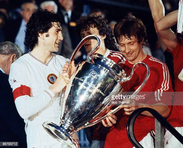 Dennis Mortimer and Kenny Swain of Aston Villa celebrate with the trophy after victory in the Aston Villa v Bayern Munich European Cup Final played...