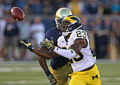 Dennis Norfleet of the Michigan Wolverines makes a catch in front of Jaylon Smith of the Notre Dame Fighting Irish at Notre Dame Stadium on September...