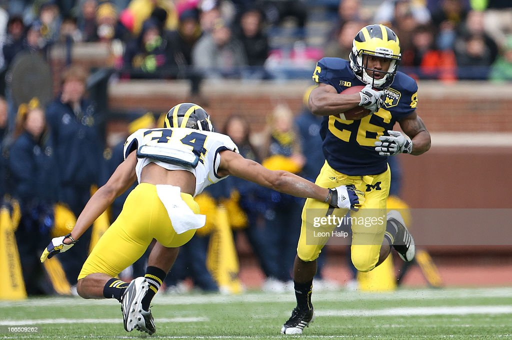 Dennis Norfleet #26 runs for a short gain as Brendan Gibbons #34 attempts to make the stop during the Michigan Spring Game at Michigan Stadium on April 13, 2013 in Ann Arbor, Michigan.