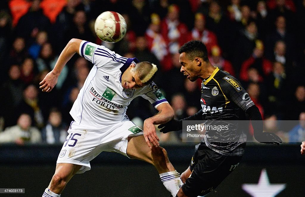 Dennis Odoi of Sporting Lokeren scores an own goal next to Aleksandar Mitrovic (L) of RSC Anderlecht during the Jupiler League match between Sporting Club Lokeren Oost-Vlaanderen and RSC Anderlecht on February 21, 2014 in Lokeren, Belgium.