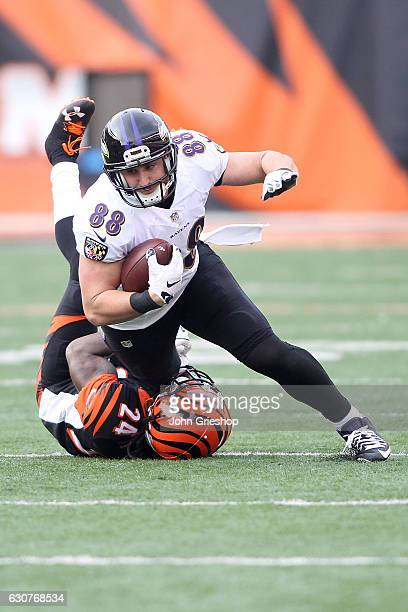 Dennis Pitta of the Baltimore Ravens is tackled by Adam Jones of the Cincinnati Bengals during the fourth quarter at Paul Brown Stadium on January 1...