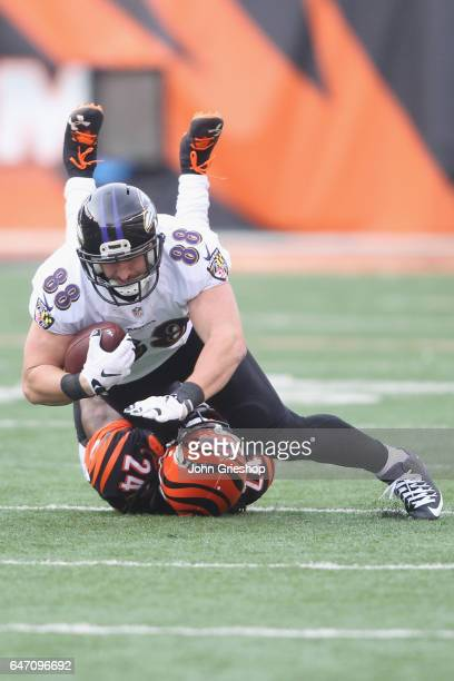 Dennis Pitta of the Baltimore Ravens runs the football upfield against Adam Jones of the Cincinnati Bengals during their game at Paul Brown Stadium...