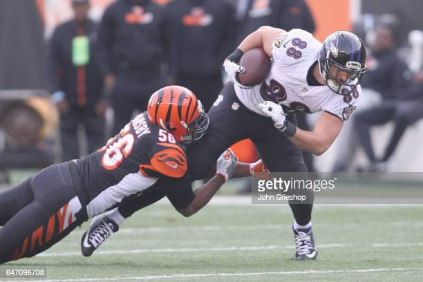 Dennis Pitta of the Baltimore Ravens runs the football upfield against Karlos Dansby of the Cincinnati Bengals during their game at Paul Brown...