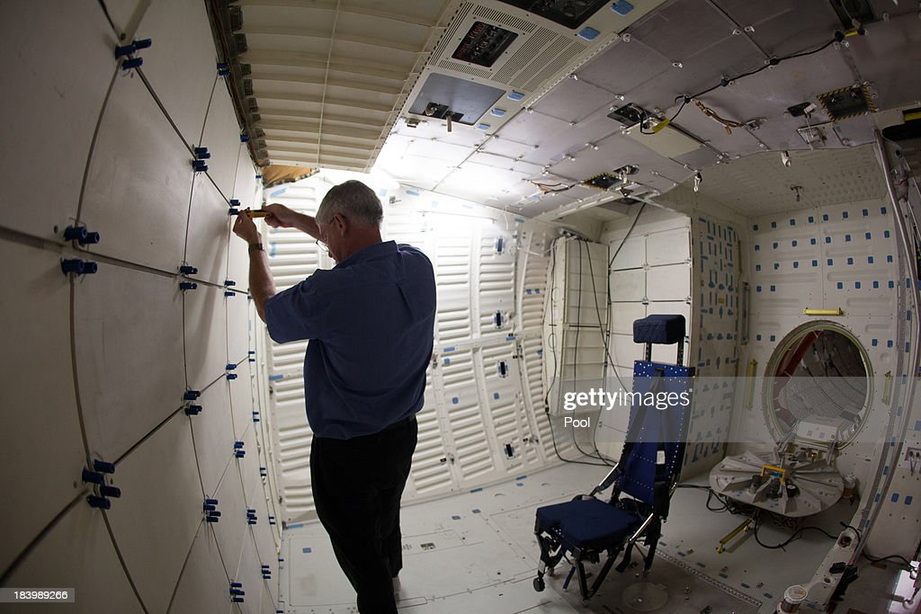 Dennis R. Jenkins of the California Science Center opens a compartment inside the mid-deck of space Shuttle Endeavour, celebrating the one year anniversary of Endeavour's journey through the street of Los Angeles, on October 10, 2013 in Los Angeles, California. Lynda Oschin, whose foundation helped to bring the shuttle to Los Angeles, formed the Mr. and Mrs. Samuel and Lynda Oschin Foundation, formed in honor of Oschin's late husband, a Los Angeles businessman and philanthropist. The blue chair (R) was where an astronaut would have sat. After they were done with the chairs, the chairs could be moved and collapsed to create more space in the mid-deck.