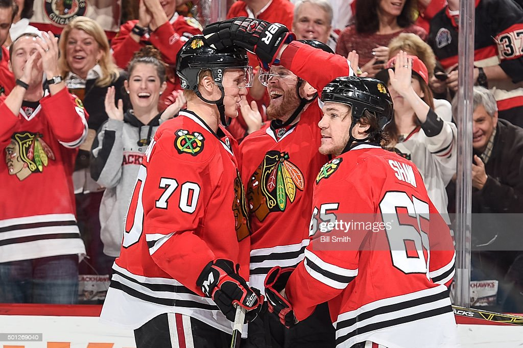 Dennis Rasmussen #70, <a gi-track='captionPersonalityLinkClicked' href=/galleries/search?phrase=Bryan+Bickell&family=editorial&specificpeople=241498 ng-click='$event.stopPropagation()'>Bryan Bickell</a> #29 and <a gi-track='captionPersonalityLinkClicked' href=/galleries/search?phrase=Andrew+Shaw+-+Joueur+de+hockey+sur+glace&family=editorial&specificpeople=10568695 ng-click='$event.stopPropagation()'>Andrew Shaw</a> #65 of the Chicago Blackhawks celebrate after Rasmussen scored against the Vancouver Canucks in the third period of the NHL game at the United Center on December 13, 2015 in Chicago, Illinois.