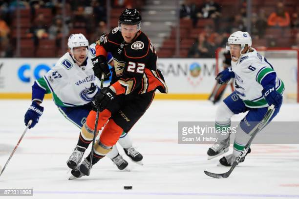 Dennis Rasmussen of the Anaheim Ducks skates past Brock Boeser and Sven Baertschi of the Vancouver Canucks during the first period of a game at Honda...