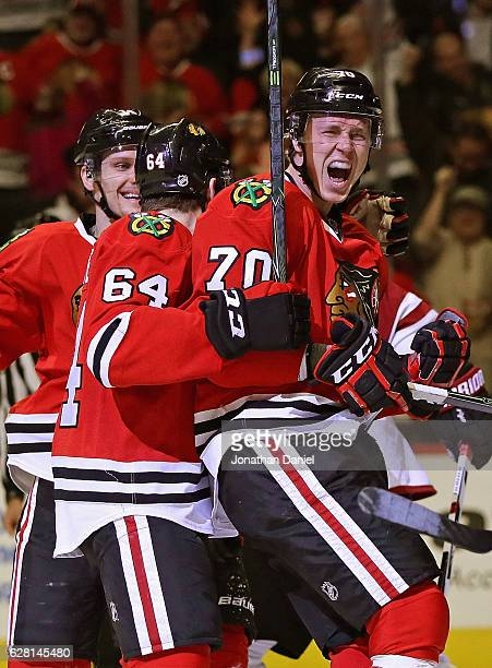 Dennis Rasmussen of the Chicago Blackhawks celebrates his second period goal with Richard Panik and Tyler Motte at the United Center on December 6...