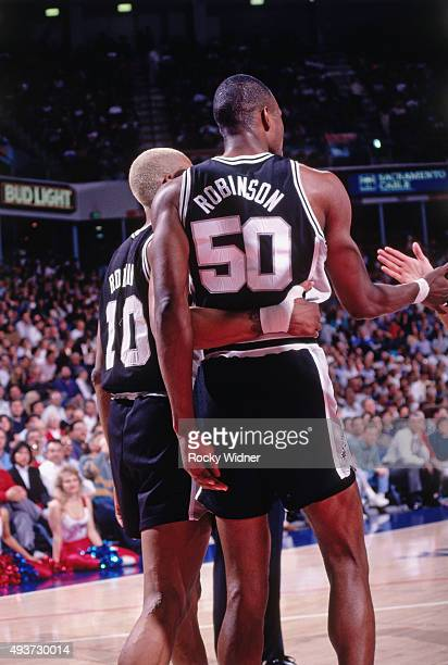 Dennis Rodman and David Robinson of the San Antonio Spurs hug gainst the Sacramento Kings on March 24 1994 at Arco Arena in Sacramento California...