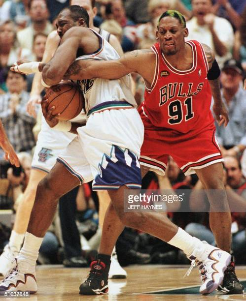 Dennis Rodman of the Chicago Bulls gets his arm caught by Karl Malone of the Utah Jazz 14 June as Rodman tries for the ball during game six of the...