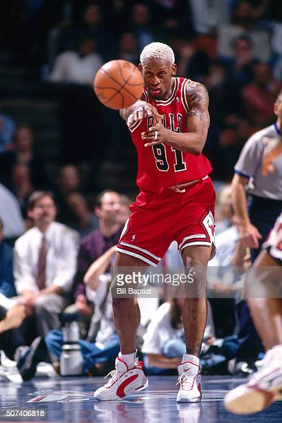 Dennis Rodman of the Chicago Bulls passes the ball against the Houston Rockets on January 30 1996 at the Summit in Houston Texas NOTE TO USER User...