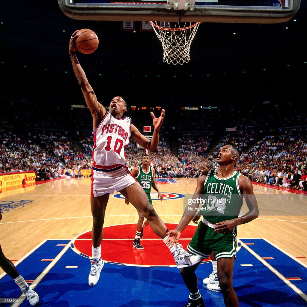 Dennis Rodman of the Detroit Pistons grabs a rebound against Reggie Lewis of the Boston Celtics in a game played in 1990 at The Palace of Auburn...