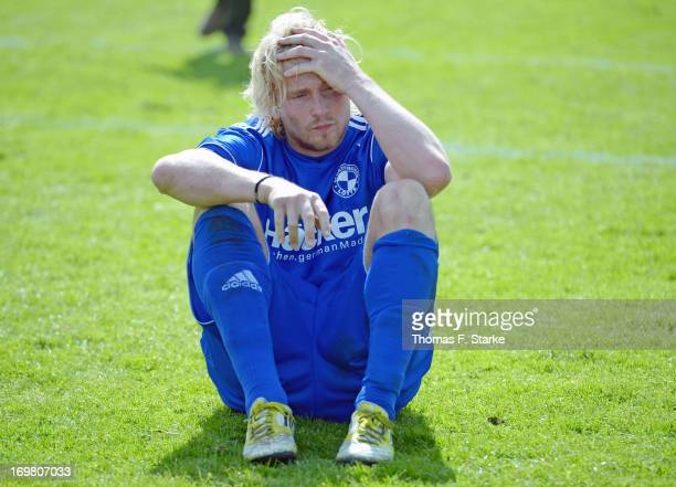 Dennis Schmidt of Lotte sits dejected on the pitch after loosing the Regionalliga Playoff Second Leg match between Sportfreunde Lotte and...