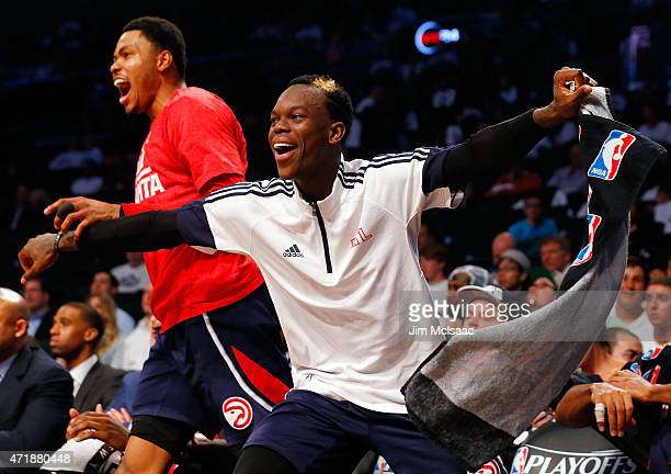 Dennis Schroder and Kent Bazemore of the Atlanta Hawks celebrate from the bench late in game six in the first round of the 2015 NBA Playoffs against...