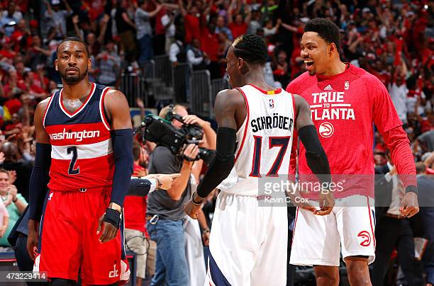 Dennis Schroder and Kent Bazemore of the Atlanta Hawks celebrate the win as John Wall of the Washington Wizards walks off the court after Game Five...