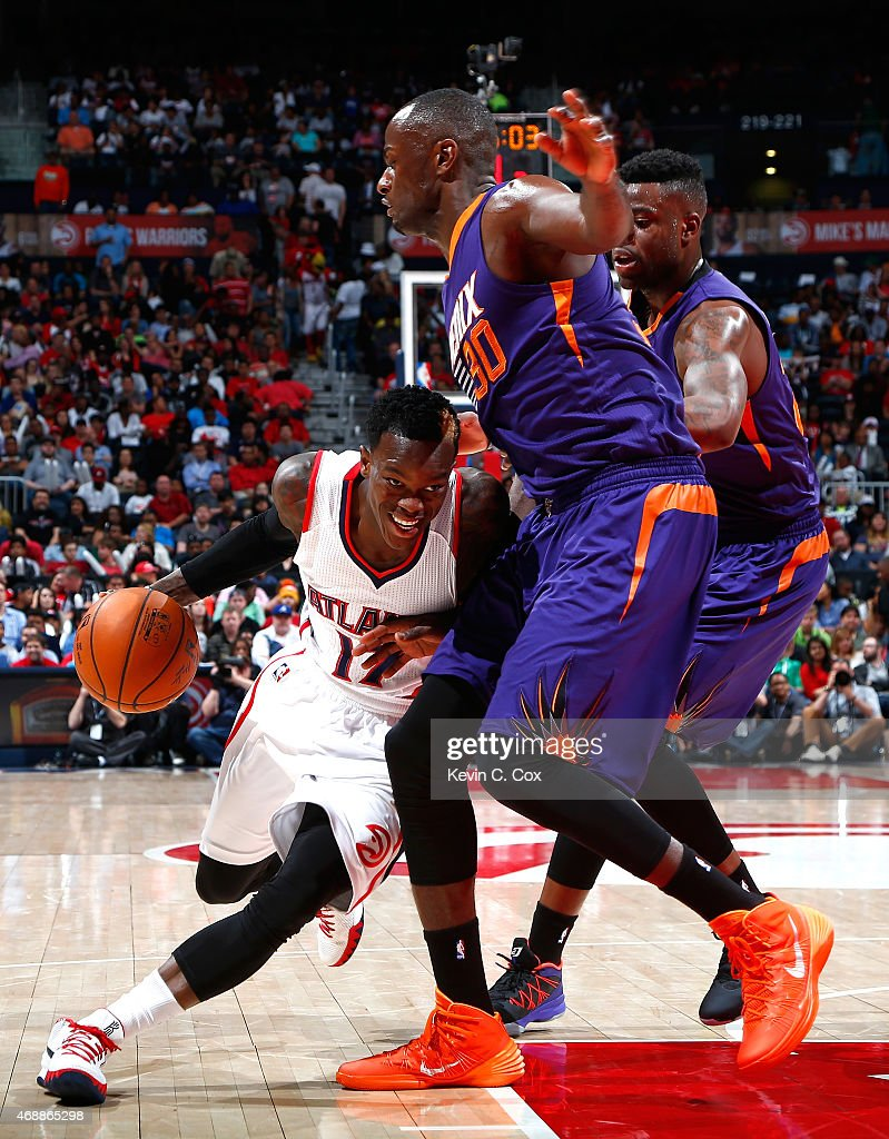 Dennis Schroder #17 of the Atlanta Hawks drives against Earl Barron #30 and Reggie Bullock #25 of the Phoenix Suns at Philips Arena on April 7, 2015 in Atlanta, Georgia.