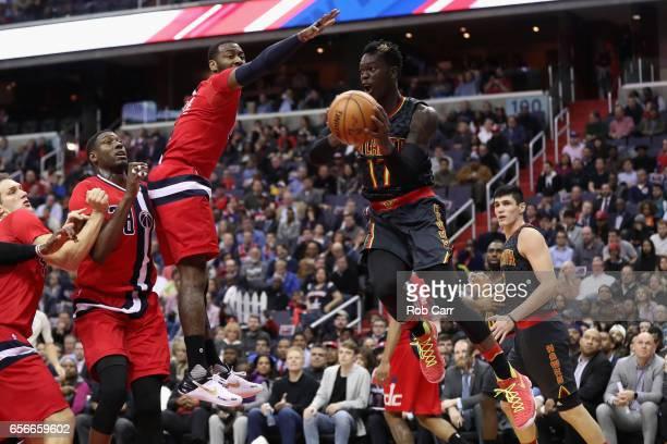 Dennis Schroder of the Atlanta Hawks looks to pass around John Wall of the Washington Wizards at Verizon Center on March 22 2017 in Washington DC...