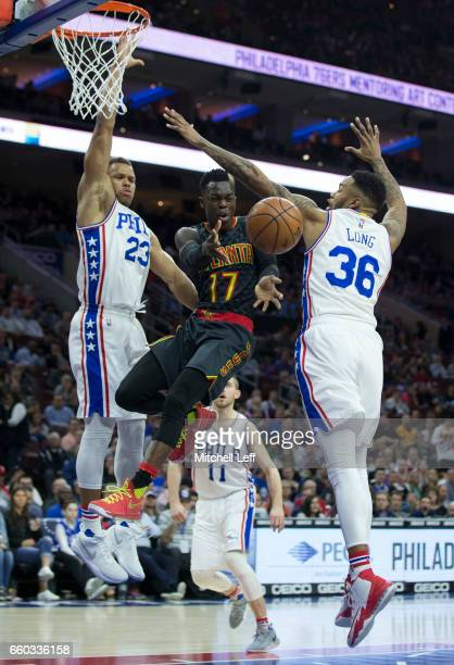 Dennis Schroder of the Atlanta Hawks passes the ball against Justin Anderson and Shawn Long of the Philadelphia 76ers in the first quarter at the...