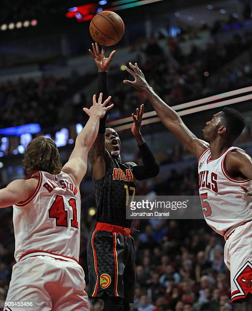 Dennis Schroder of the Atlanta Hawks shoots over Cameron Bairstow and Bobby Portis of the Chicago Bulls at the United Center on February 10 2016 in...
