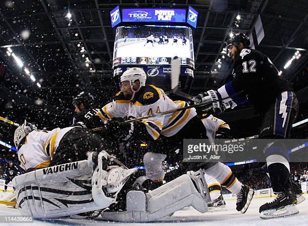 Dennis Seidenberg falls over Tim Thomas of the Boston Bruins as they vie for position with Simon Gagne of the Tampa Bay Lightning in Game Three of...