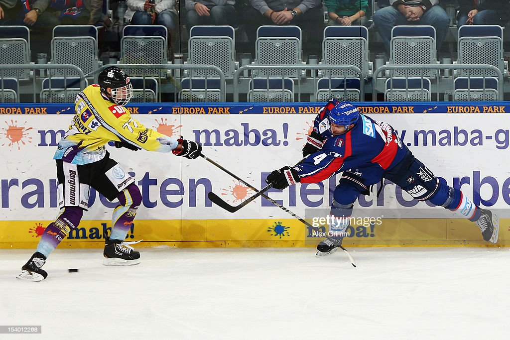 Dennis Seidenberg (R) of Mannheim is challenged by Kevin Orendorz of Krefeld during the DEL match between Adler Mannheim and Krefeld Pinguine at SAP-Arena on October 12, 2012 in Mannheim, Germany.