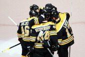 Dennis Seidenberg of the Boston Bruins celebrates his first period goal against the Tampa Bay Lightning with teammates in Game Two of the Eastern...