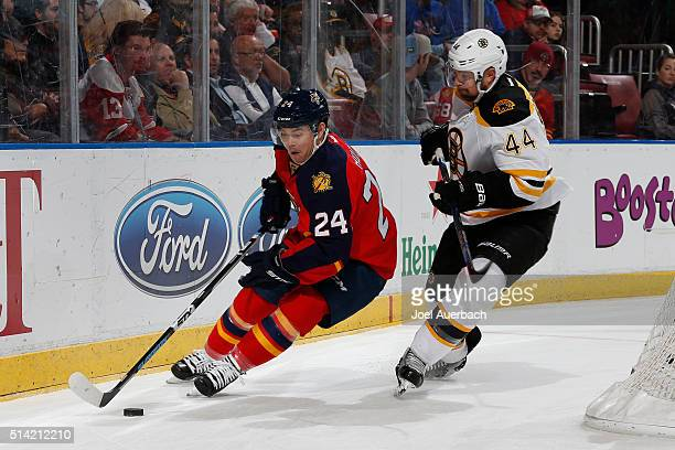 Dennis Seidenberg of the Boston Bruins defends against Jiri Hudler of the Florida Panthers as he circles the net with the puck during first period...
