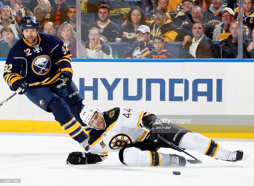 Dennis Seidenberg #44 of the Boston Bruins falls to the ice in front of John Scott #32 of the Buffalo Sabres at First Niagara Center on October 23, 2013 in Buffalo, New York.