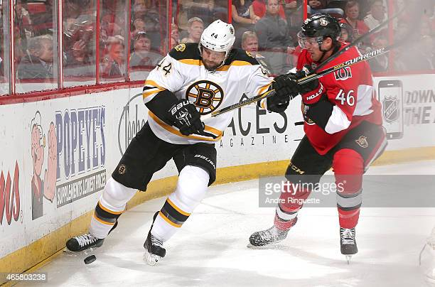Dennis Seidenberg of the Boston Bruins fends off Patrick Wiercioch of the Ottawa Senators as they battle for the puck along the boards at Canadian...