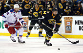 Dennis Seidenberg of the Boston Bruins keeps the puck from Rick Nash of the New York Rangers in the first period at the TD Garden on March 28 2015 in...