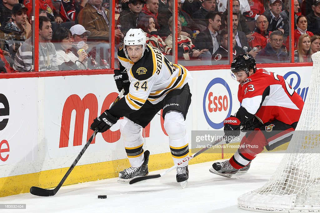 Dennis Seidenberg #44 of the Boston Bruins makes a pass as Kaspars Daugavins #23 of the Ottawa Senators reaches for the puck, during an NHL game at Scotiabank Place, on March 11, 2013 in Ottawa, Ontario, Canada.