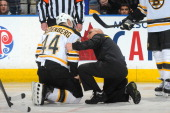 Dennis Seidenberg of the Boston Bruins receives medical attention in a game against the Edmonton Oilers on December 12 2013 at Rexall Place in...