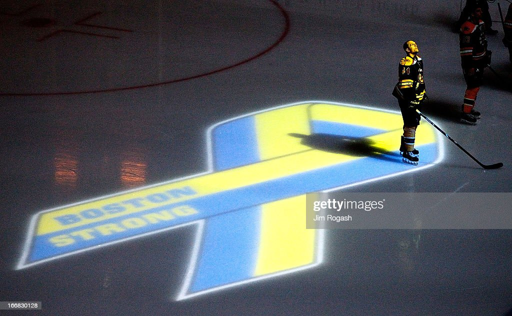 Dennis Seidenberg #44 of the Boston Bruins stands near aa projection of the Boston Marathon Memorial Ribbon seen on the ice during pre game ceremonies in remembrance of the Boston Marathon bombing victims before a game between the Buffalo Sabres and the Boston Bruins at TD Garden on April 17, 2013 in Boston, Massachusetts.