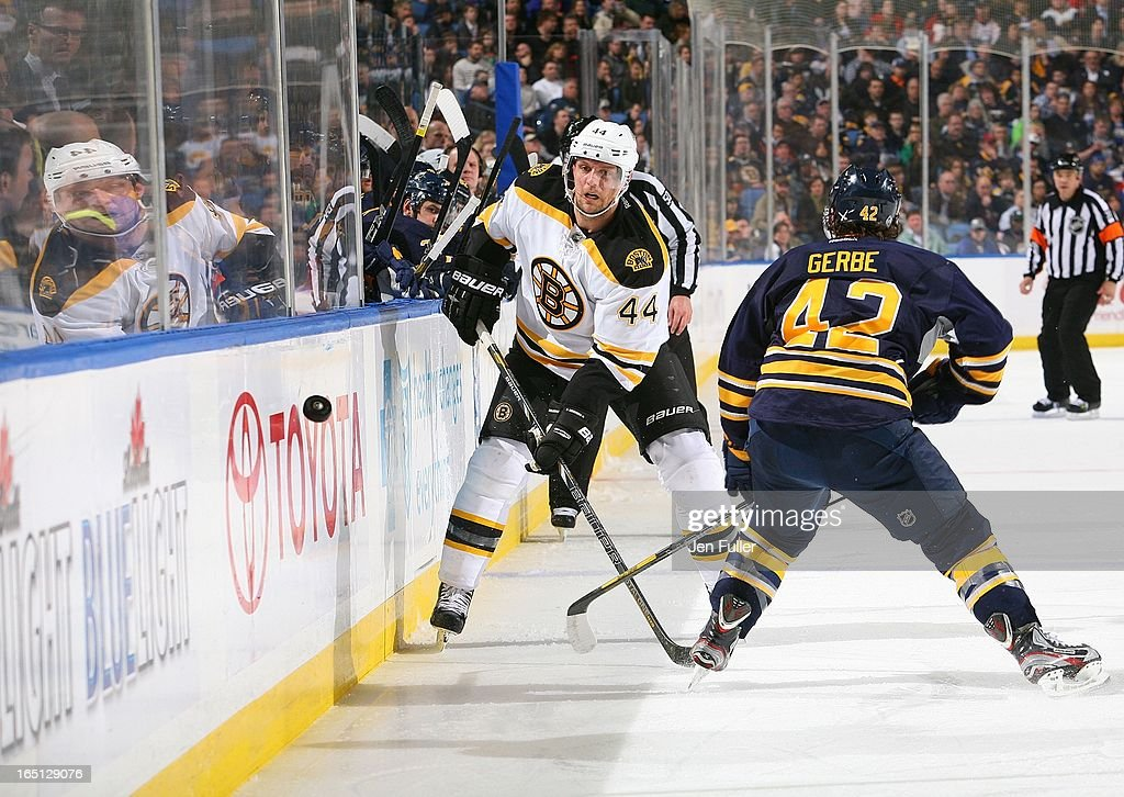 <a gi-track='captionPersonalityLinkClicked' href=/galleries/search?phrase=Dennis+Seidenberg&family=editorial&specificpeople=204616 ng-click='$event.stopPropagation()'>Dennis Seidenberg</a> #44 of the Boston Bruins tips the puck past <a gi-track='captionPersonalityLinkClicked' href=/galleries/search?phrase=Nathan+Gerbe&family=editorial&specificpeople=697084 ng-click='$event.stopPropagation()'>Nathan Gerbe</a> #42 of the Buffalo Sabres on March 31, 2013 at the First Niagara Center in Buffalo, New York.
