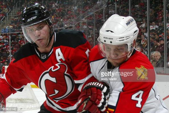 Dennis Seidenberg of the Florida Panthers and Colin White of the New Jersey Devils battle for position during their game at the Prudential Center on...