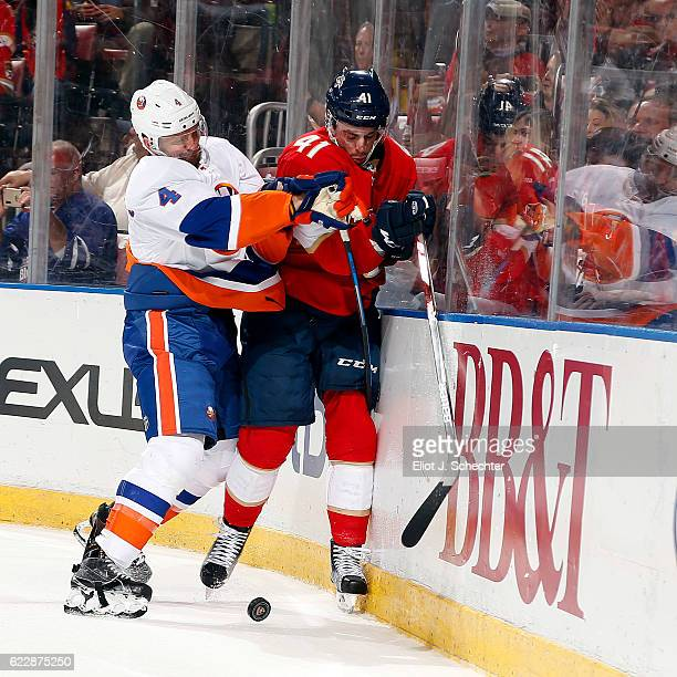 Dennis Seidenberg of the New York Islanders check Greg McKegg of the Florida Panthers into the boards during first period action at the BBT Center on...
