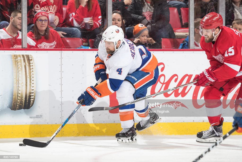Dennis Seidenberg #4 of the New York Islanders skates with the puck followed by Riley Sheahan #15 of the Detroit Red Wings during an NHL game at Joe Louis Arena on February 3, 2017 in Detroit, Michigan. The Wings defeated the Islanders 5-4.