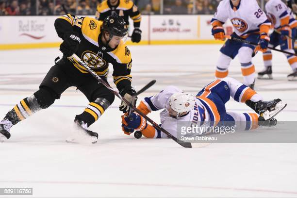 Dennis Seidenebrg of the New York Islanders fights for the puck against Anders Bjork of the Boston Bruins at the TD Garden on December 9 2017 in...