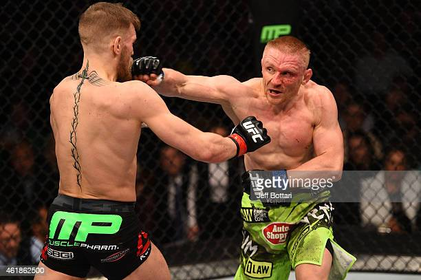 Dennis Siver of Germany punches Conor McGregor of Ireland in their featherweight fight during the UFC Fight Night event at the TD Garden on January...
