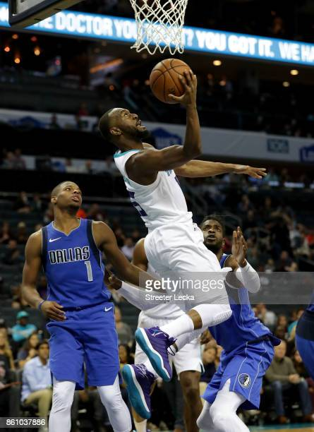 Dennis Smith Jr #1 of the Dallas Mavericks watches as Kemba Walker of the Charlotte Hornets drives to the basket during their game at Spectrum Center...