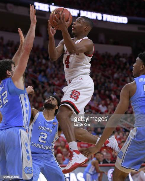 Dennis Smith Jr #4 of the North Carolina State Wolfpack goes to the basket against Luke Maye and Joel Berry II of the North Carolina Tar Heels at PNC...