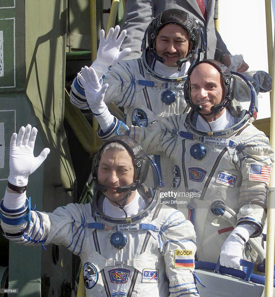 Dennis Tito, center, the world's first space tourist, waves while boarding the Soyuz TM-32 spaceship April 28, 2001 at the Baikonur cosmodrome in Kazakhstan. Tito is joined by Russian cosmonauts Talgat Musabayev, top, and Yuri Baturin. Tito is paying the Russian space agency $20 million for the six-day journey to the International Space Station.