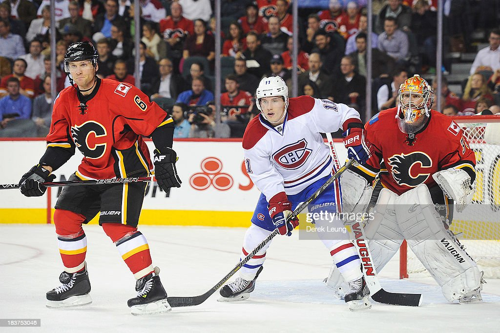 Dennis Wideman #6 and Joey MacDonald #35 of the Calgary Flames defend the net against Brendan Gallagher #11 of the Montreal Canadiens during an NHL game at Scotiabank Saddledome on October 9, 2013 in Calgary, Alberta, Canada.