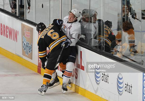 Dennis Wideman of the Boston Bruins checks against Ales Hemsky of the Edmonton Oilers at the TD Garden on October 31 2009 in Boston Massachusetts