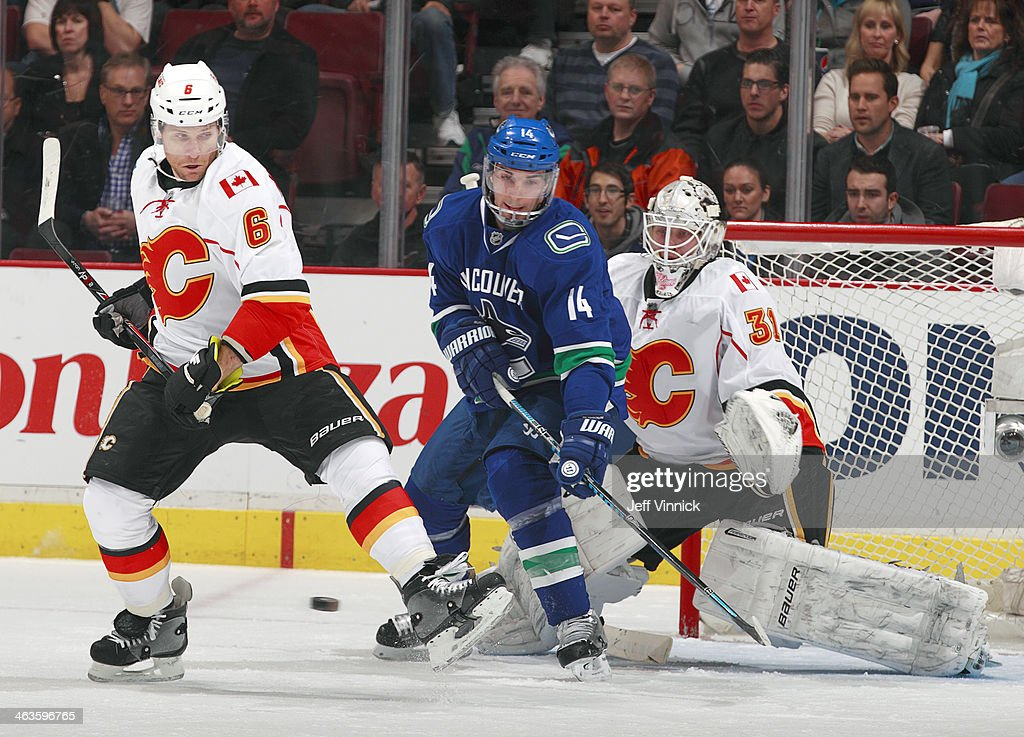 Dennis Wideman #6 of the Calgary Flames, Alexandre Burrows #14 of the Vancouver Canucks and Karri Ramo #31 of the Flames eye the puck during their NHL game at Rogers Arena January 18, 2014 in Vancouver, British Columbia, Canada.