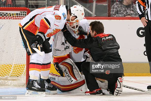 Dennis Wideman of the Calgary Flames and a team trainer check on the condition of goalie Chad Johnson during the third period against the Arizona...