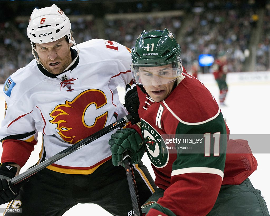 Dennis Wideman #6 of the Calgary Flames and Zach Parise #11 of the Minnesota Wild skate after the puck during the game on March 3, 2014 at Xcel Energy Center in St Paul, Minnesota.