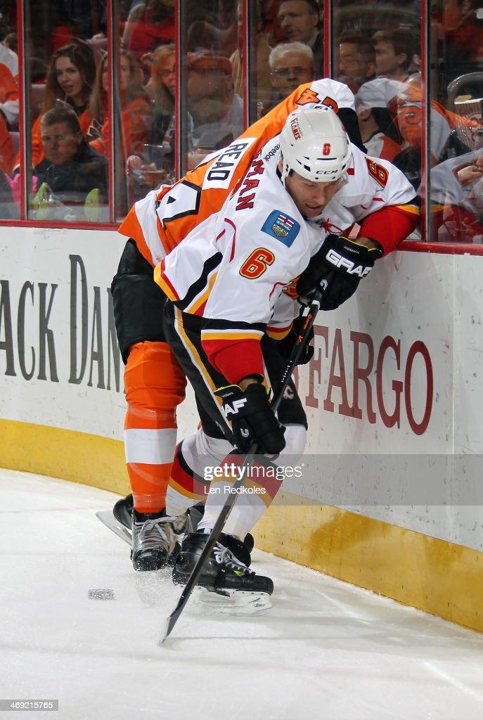 Dennis Wideman #6 of the Calgary Flames battles for the puck along the boards against Matt Read #24 of the Philadelphia Flyers on February 8, 2014 at the Wells Fargo Center in Philadelphia, Pennsylvania.