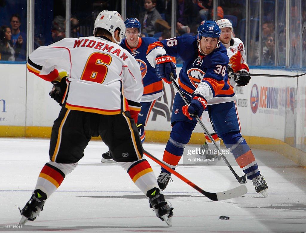 Dennis Wideman #6 of the Calgary Flames defends against Eric Boulton #36 of the New York Islanders at Nassau Veterans Memorial Coliseum on February 6, 2014 in Uniondale, New York. The Flames defeated the Islanders 4-2.