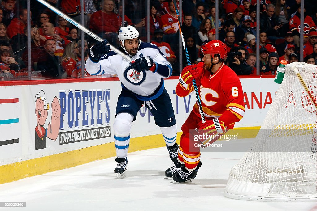 Dennis Wideman #6 of the Calgary Flames skates against Dustin Byfuglien #33 of the Winnipeg Jets during an NHL game on December 10, 2016 at the Scotiabank Saddledome in Calgary, Alberta, Canada.